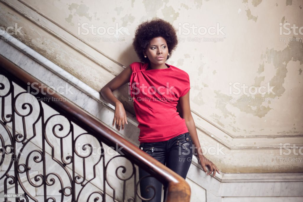Thoughtful cuban woman standing on steps against wall stock photo