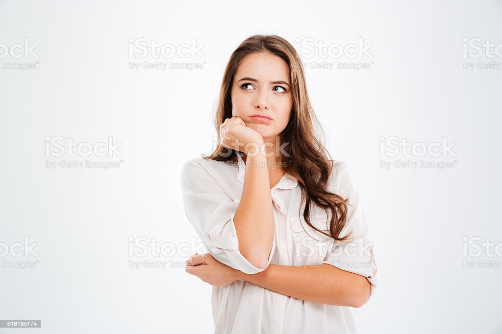 Thoughtful cute young woman standing and thinking stock photo