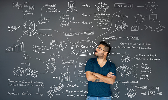 Happy Latin American thoughtful entrepreneur looking at the business plan behind him on a blackboard