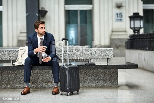 Thoughtful businessman having coffee while holding phone. Male is sitting by wheeled luggage on concrete bench. He is in formalwear.