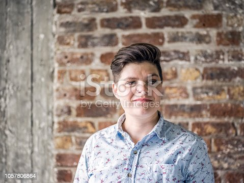 Thoughtful female architect and entrepreneur standing at construction site. Young woman is looking away against brick wall. She is in floral patterned shirt.