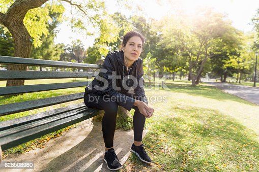 Thoughtful female athlete sitting on bench at park. Young woman is relaxing after workout. She is in sportswear on sunny day.