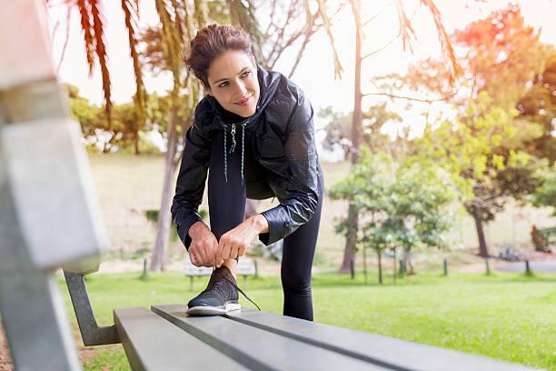 thoughtful female athlete tying shoelace on bench - sitzbank schuhe stock-fotos und bilder