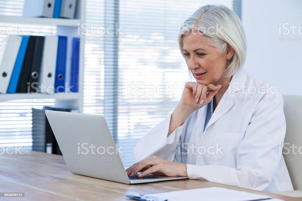 Nachdenklich Ärztin arbeitet auf ihrem laptop – Foto