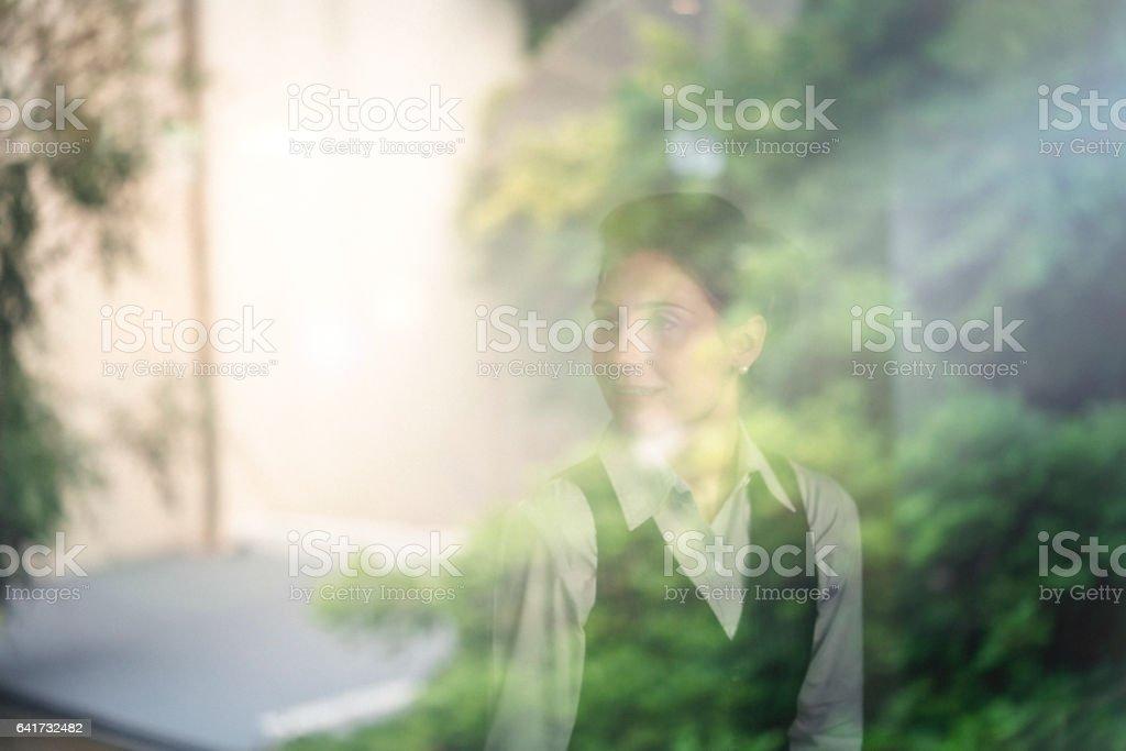 Thoughtful female entrepreneur seen through window stock photo