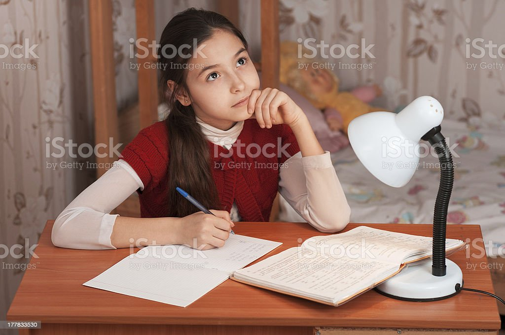 thoughtful girl doing homework at the table royalty-free stock photo