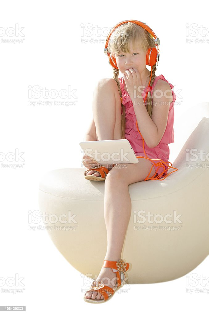 Thoughtful girl doing homework with tablet computer and listenin royalty-free stock photo
