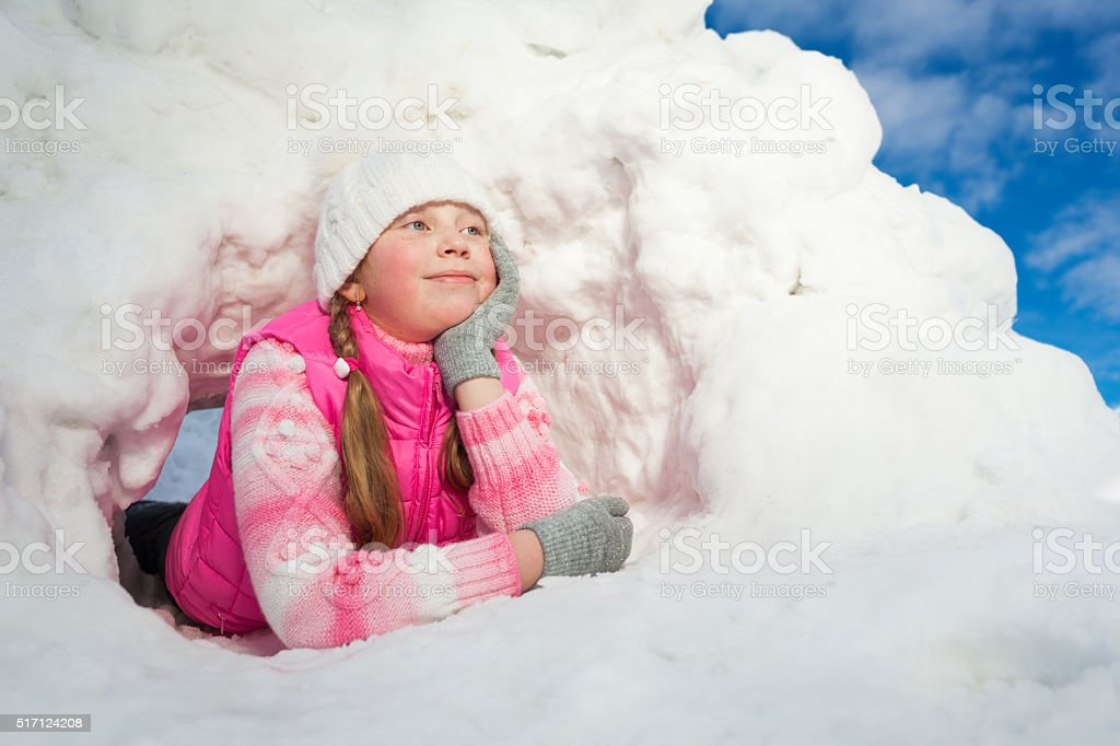 Thoughtful girl laying at the snow hole stock photo