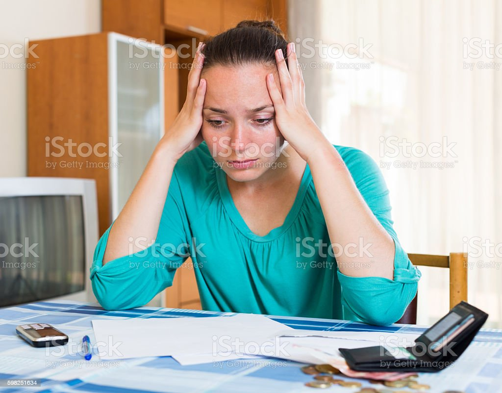 thoughtful girl sits with her bills on the table stock photo