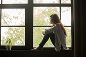 Thoughtful girl sitting on sill embracing knees looking at window
