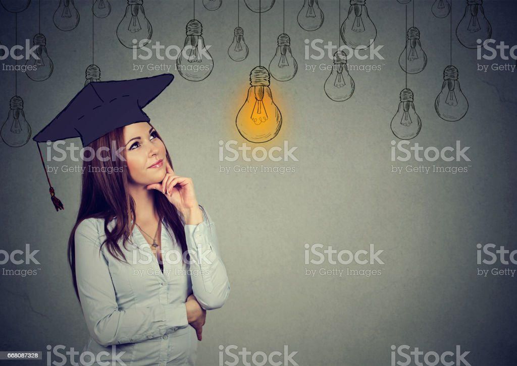Thoughtful graduate student young woman in cap stock photo