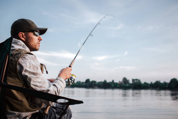 thoughtful guy is sitting at the edge of water and looking to the right. he holds fly rod in hands. it is evening and chilly outside. - fishing industry stock pictures, royalty-free photos & images
