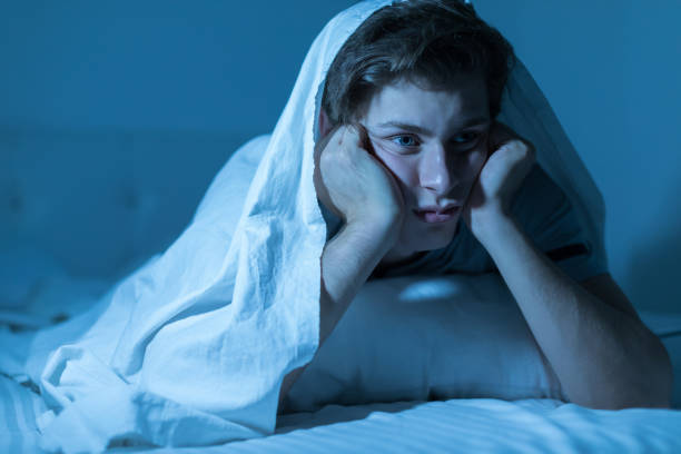 Thoughtful guy suffers from insomnia stock photo