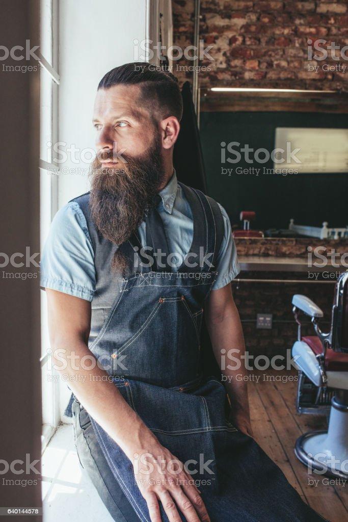 Thoughtful hairdresser sitting on window sill in salon stock photo