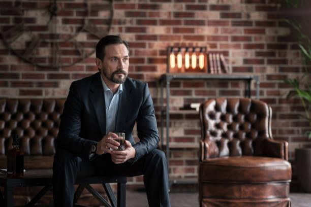 thoughtful handsome man drinking whisky - ledersessel braun stock-fotos und bilder
