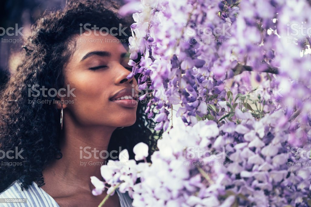 Thoughtful happy young black woman surrounded by flowers stock photo