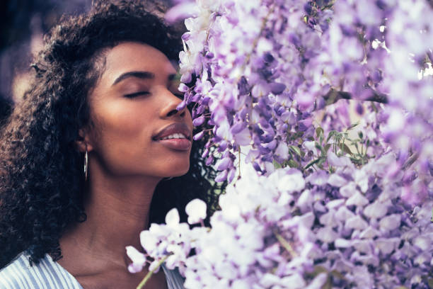 thoughtful happy young black woman surrounded by flowers - annusare foto e immagini stock