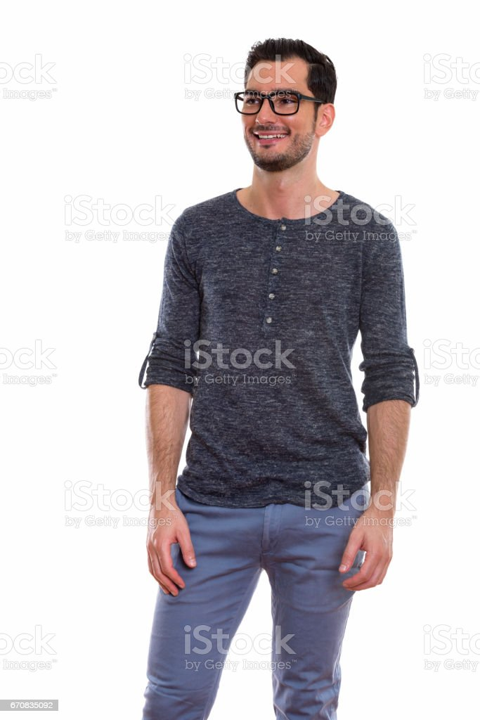 Thoughtful happy young handsome man smiling and standing while wearing eyeglasses stock photo