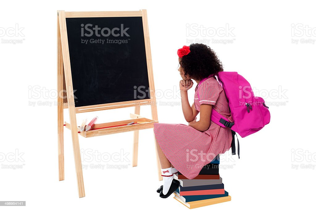 Thoughtful kid sitting in front of blackboard royalty-free stock photo