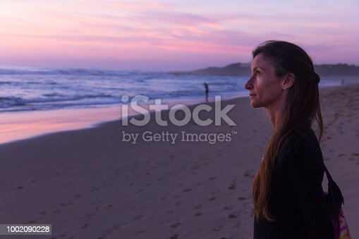 Lonely young woman stares contemplative at sunset by shore on beach