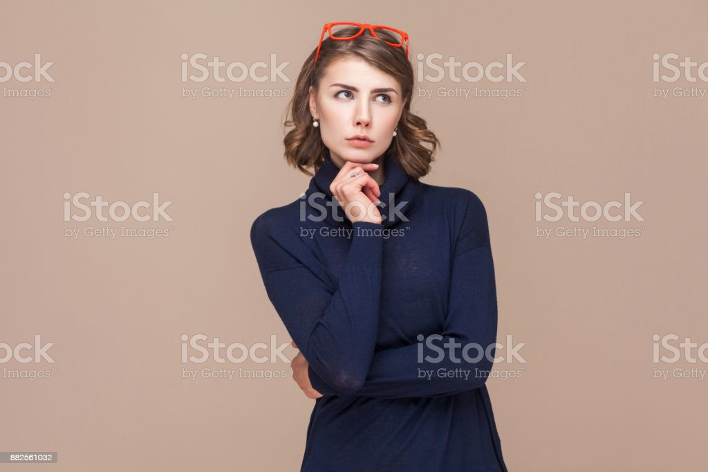 Thoughtful lady pondering and touching chin. stock photo