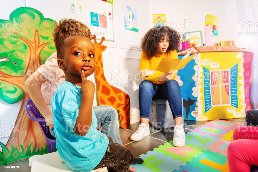 Thoughtful little black boy in the kindergarten Thoughtful little black boy in the kindergarten with teacher reading a story Book Stock Photo