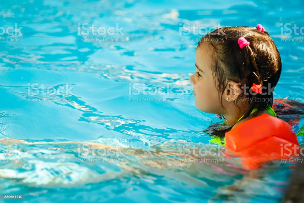 Thoughtful little girl in the pool, outdoor. stock photo