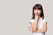 istock Thoughtful little girl looking away thinking isolated on grey background 1157139768