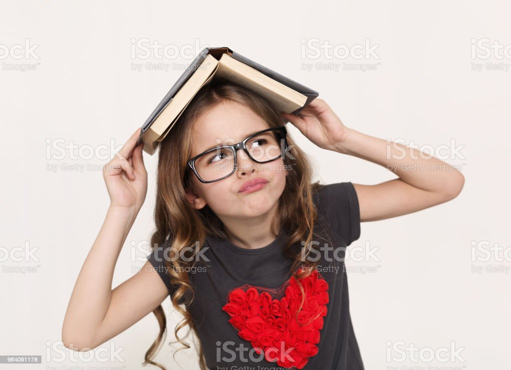 Thoughtful little girl with book over head at white background - Royalty-free Baby - Human Age Stock Photo