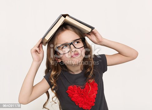 Pensive little girl in glasses and book on head on white studio background, copy space. Back to school, overworking concept