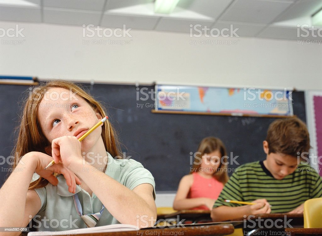 Thoughtful looking girl in classroom royalty-free stock photo