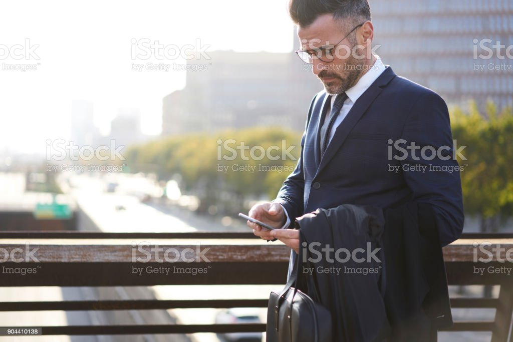 Thoughtful male entrepreneur using modern smartphone connected to 4G internet booking tickets being in business trip and making payment online on banking website while standing near copy space area stock photo