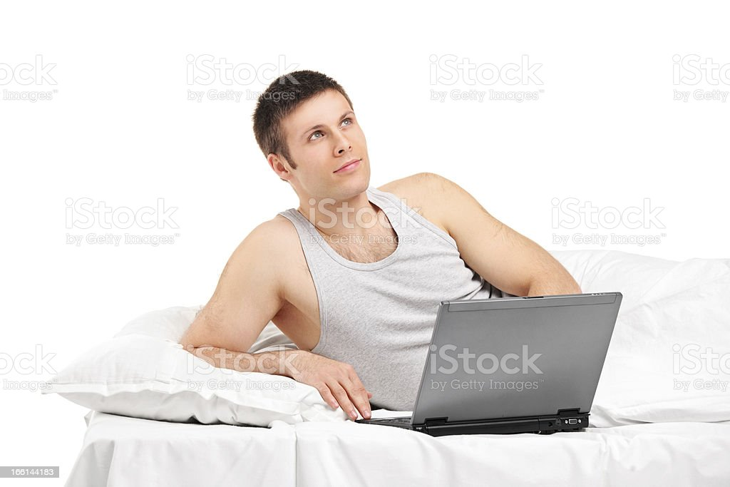Thoughtful male lying and working on a laptop royalty-free stock photo