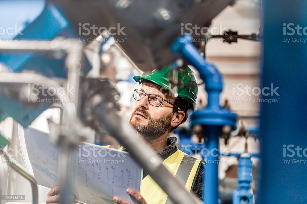 Thoughtful male worker holding document at factory stock photo