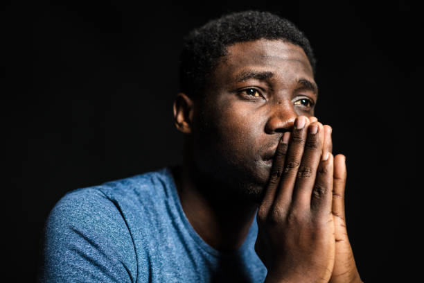 Thoughtful man against black background stock photo