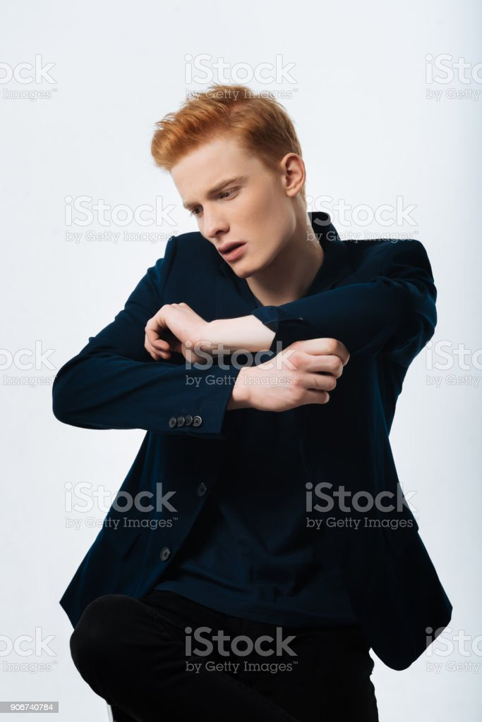 Thoughtful man buttoning up his sleeve stock photo