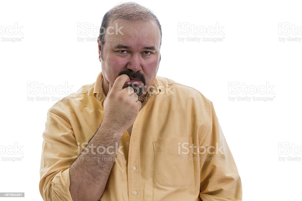 Thoughtful man chewing his finger as he debates stock photo