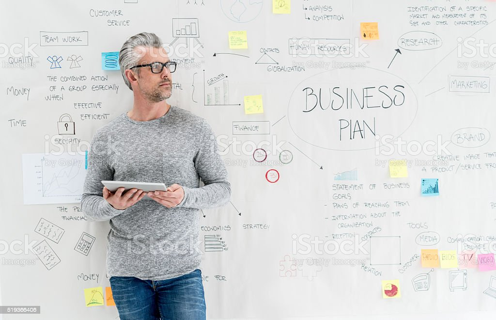 Thoughtful man creating a business plan stock photo