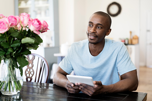 Thoughtful man holding digital tablet at home