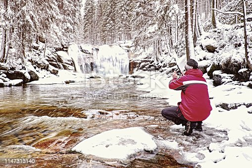 Thoughtful man in red warm jacket with smart phone in hands. Man in hat standing with raised arms bellow frozen  mountain waterfall in winter