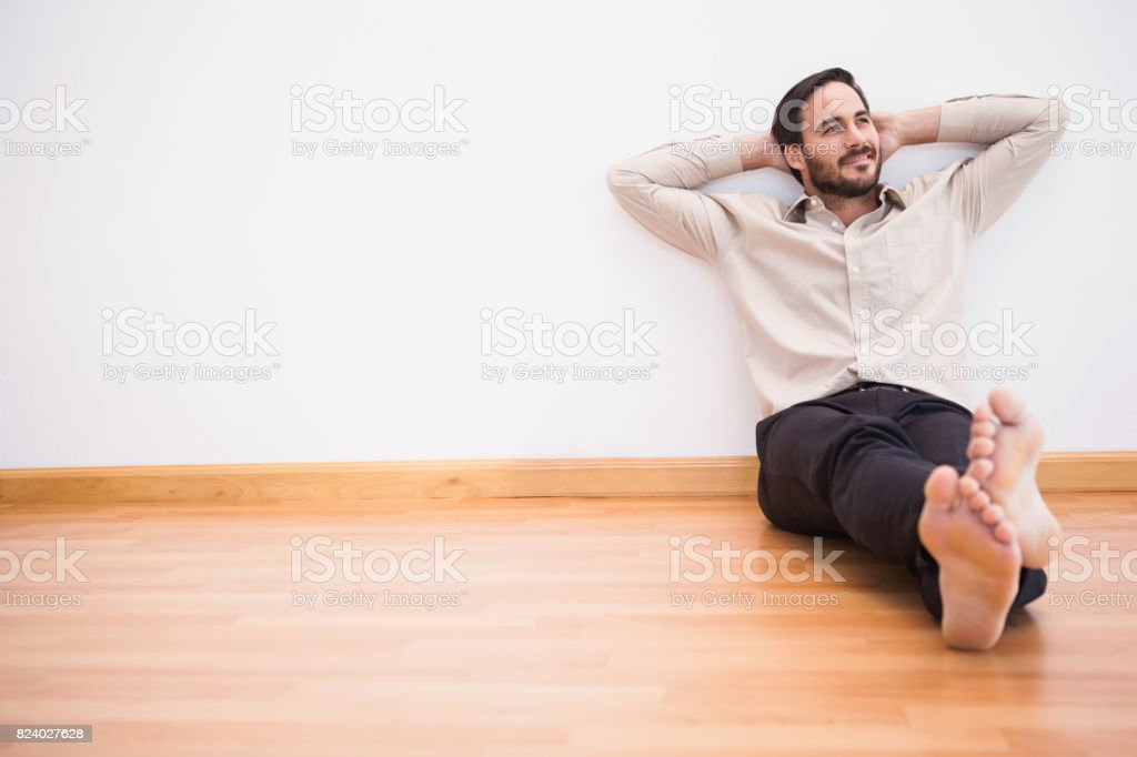 Thoughtful man leaning against wall with crossed arms stock photo