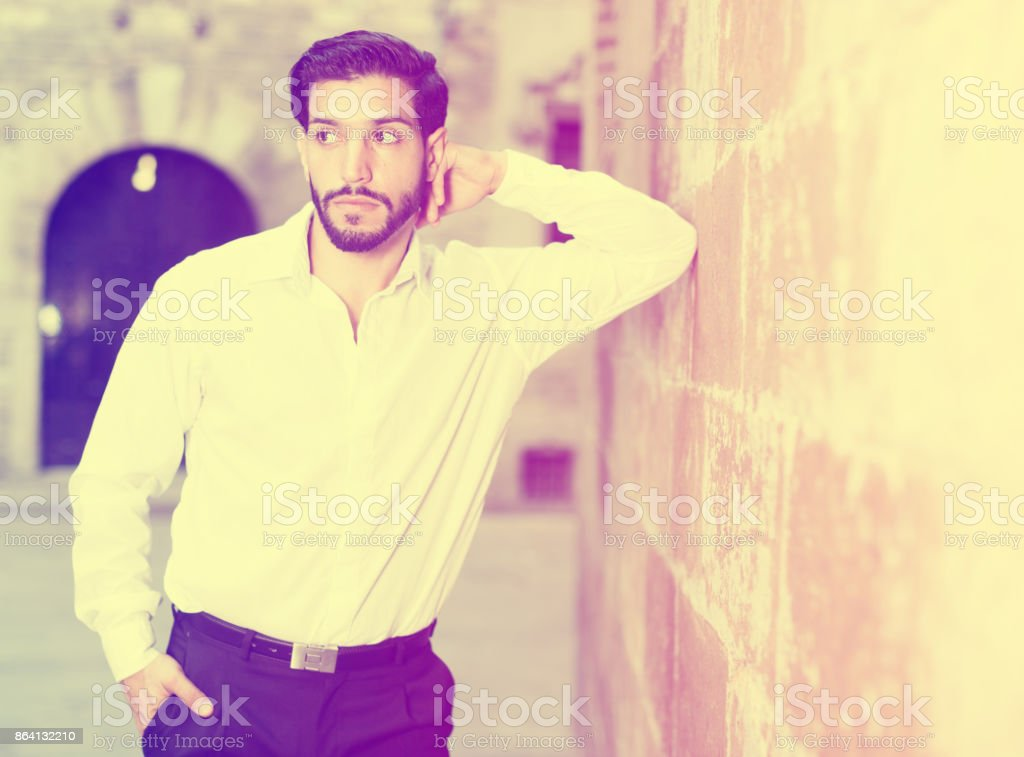 Thoughtful man leaning elbow on wall royalty-free stock photo