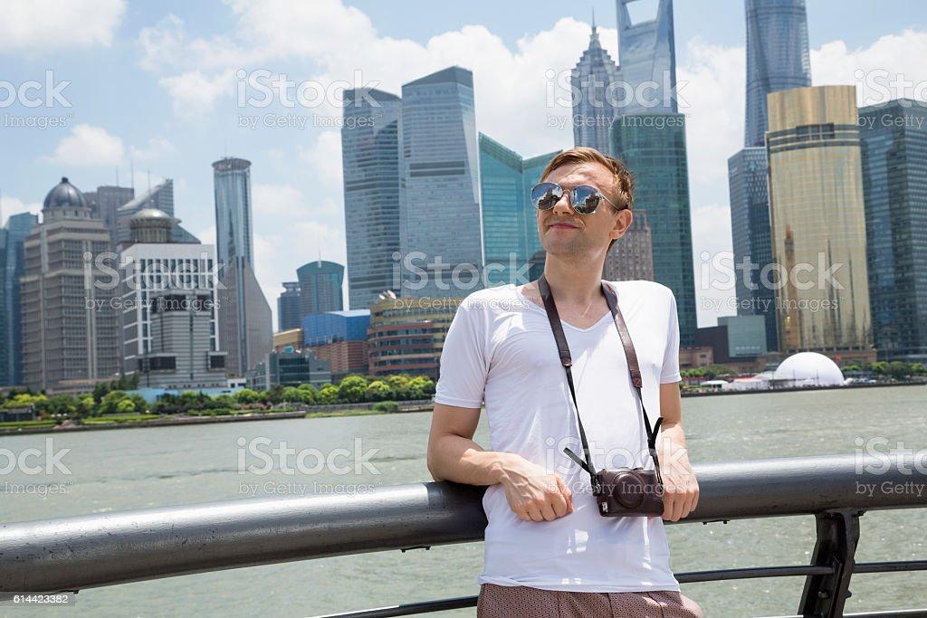 thoughtful man leaning on railing against shanghai world financial