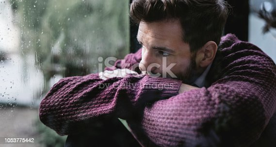 istock Thoughtful man looking out the window 1053775442