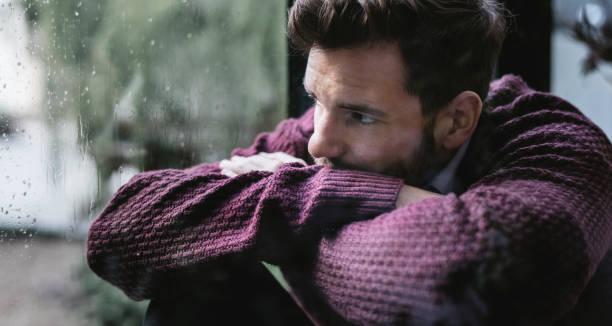nachdenklicher mann schaut aus dem fenster - depression stock-fotos und bilder