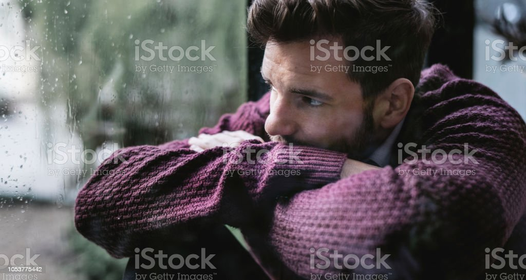 Thoughtful man looking out the window stock photo
