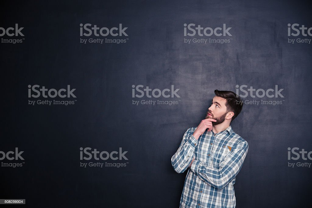 Thoughtful man looking up at copyspace stock photo