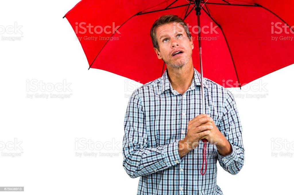 Homme pensif, regardant vers le haut tout en tenant le parapluie rouge photo libre de droits
