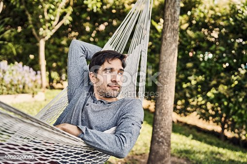 Thoughtful man lying on hammock. Mid adult male is relaxing at yard. He is wearing casuals.