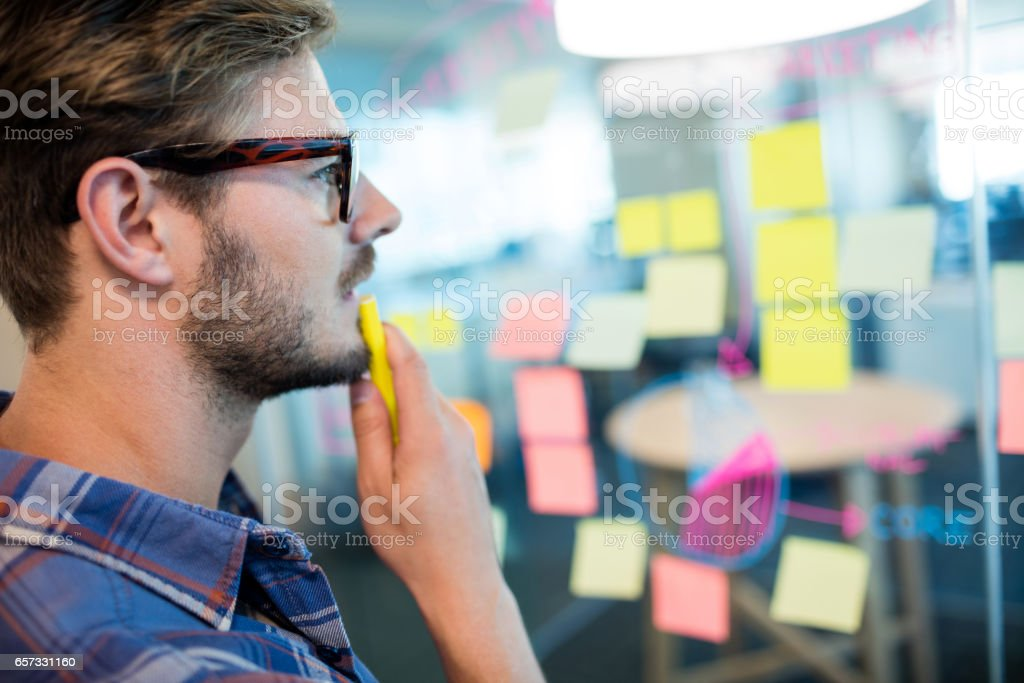 Thoughtful man reading sticky notes on the glass wall stock photo
